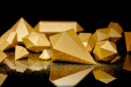 close-up view of glittering pieces of gold and golden dust reflected on black Stockfoto