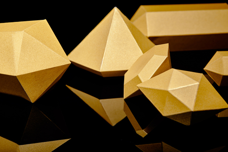 close-up view of shiny faceted golden pieces reflected on black