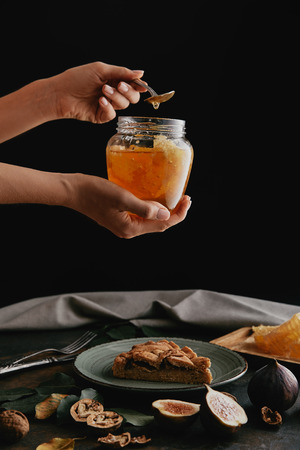 cropped shot of woman holding glass jar with honey at tabletop with piece of homemade pie