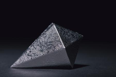 vergrote weergave van gefacetteerd stuk zilver mineraal op zwart Stockfoto