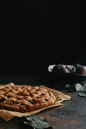 close up view of homemade pie on baking paper and fresh figs on dark tabletop Reklamní fotografie