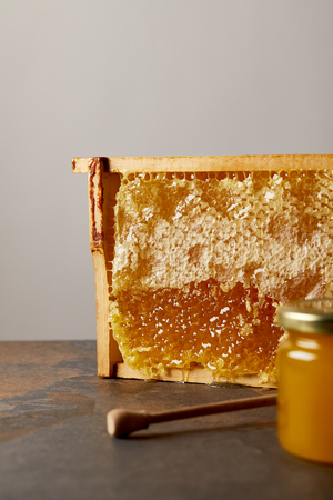 close up view of glass jar with honey, beeswax and wooden honey deeper on grey background