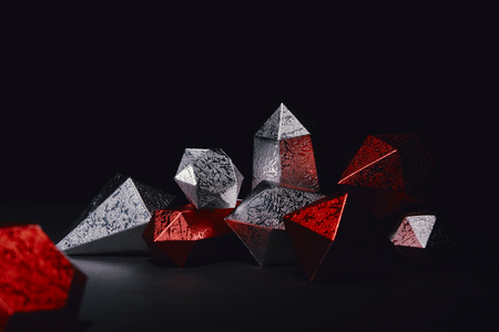 close-up view of shiny faceted red and silver gemstones on black