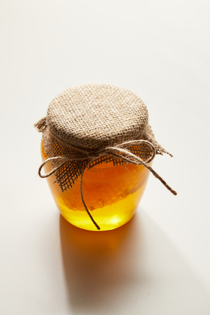 close up view of honey and beeswax in glass jar on white surface