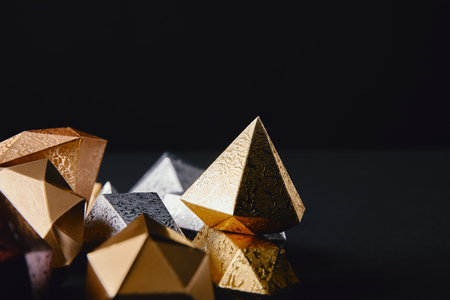 close-up view of shiny faceted golden and silver pieces on black background