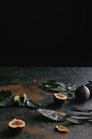 close up view of antique cutlery, green leaves and figs on grungy surface