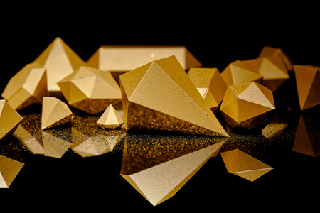 close-up view of shiny pieces of gold and golden dust reflected on black