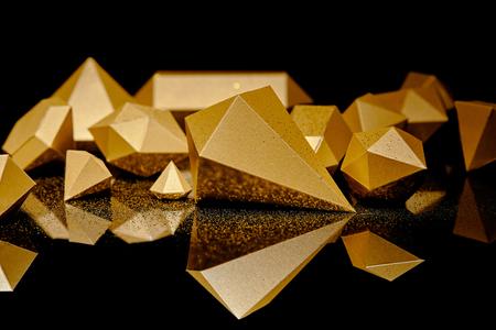 vergrote weergave van glanzende stukjes goud en gouden stof weerspiegeld op zwart