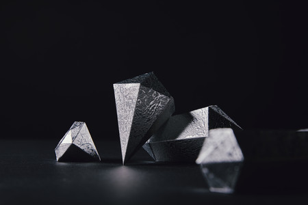 close-up view of beautiful faceted silver pieces on black