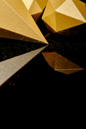 close-up view of glittering faceted pieces of gold reflected on black background
