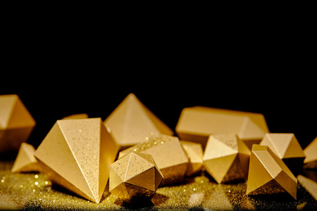 shiny faceted golden pieces and dust on black background Stockfoto