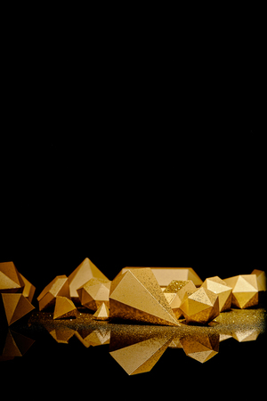 close-up view of shiny golden glittering figures reflected on black