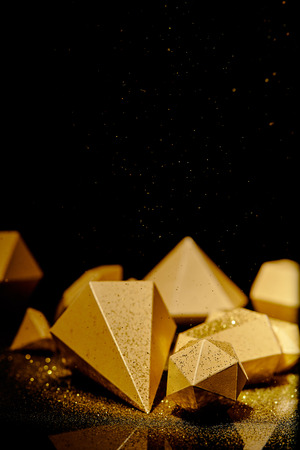 close-up view of shiny faceted golden pieces and dust on black Stockfoto