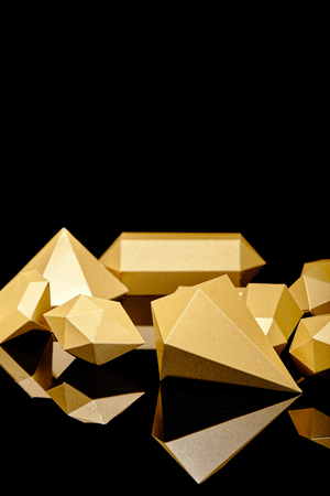 shiny faceted golden nuggets reflected on black Stock fotó