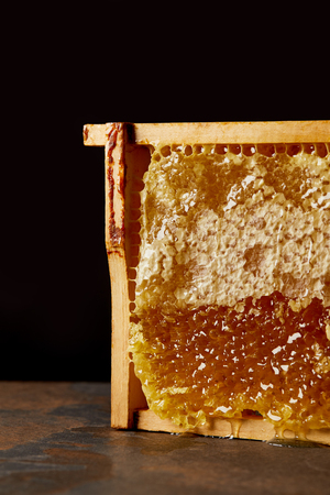 close up view of beeswax on grungy tabletop on black background 写真素材