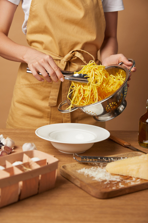 cropped shot of woman putting spaghetti into bowl with tongs from colander Stock Photo