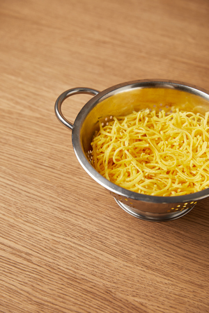 high angle view of metal colander with spaghetti on wooden table