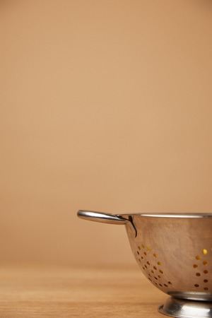 close-up shot of metal colander with macaroni on wooden table