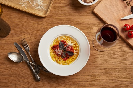 top view of plate of pasta with various ingredients and wine around on wooden table