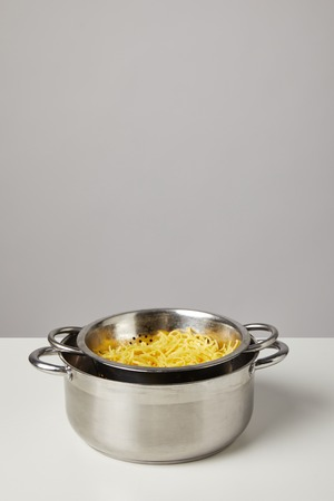 metal colander with spaghetti in pan on white table