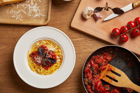 top view of plate of pasta and frying pan of tomato sauce on wooden table 写真素材