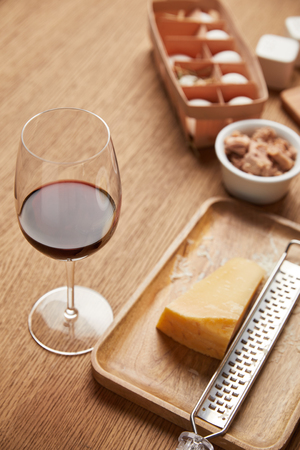 close-up shot of grated cheese and glass of red wine on wooden table