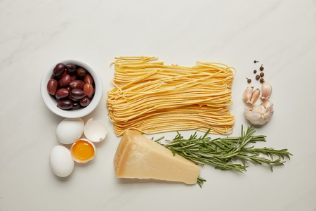 flat lat with assorted italian pasta ingredients arranged on white marble surface Banco de Imagens