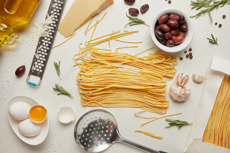 flat lay with italian pasta ingredients, ladle and grater arranged on white tabletop