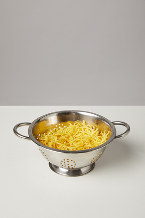 metal colander with cooked spaghetti on white table