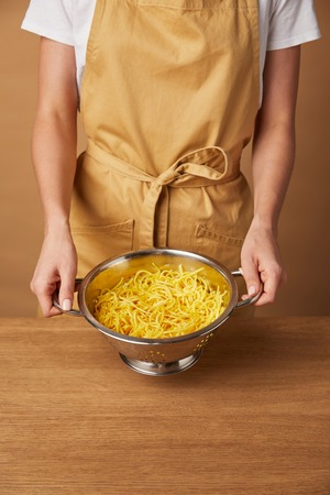 cropped shot of woman holding colander with spaghetti Stock Photo