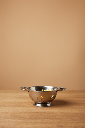 metal colander with spaghetti on wooden table in front of light brown background