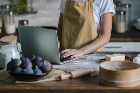 cropped shot of woman using laptop during pie preparation