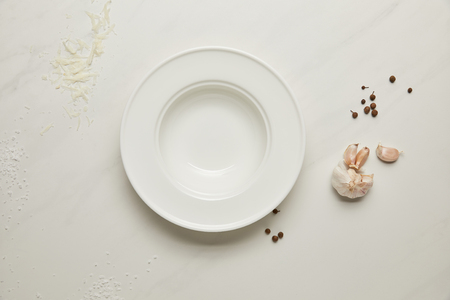 flat lay with arranged flour, grated cheese, garlic and empty plate on white tabletop