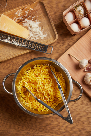 top view of spaghetti in metal colander surrounded with ingredients for pasta on wooden table Foto de archivo - 108650058