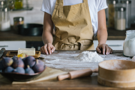cropped shot of woman in apron standing in front of rustic wooden table with pie ingredients