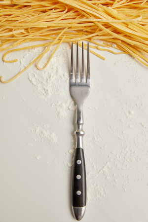 top view of fork, macaroni and flour on white surface Stock Photo
