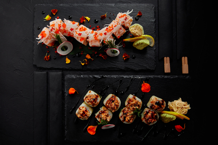 top view of roll in mamenori with shrimp, salmon and avocado in sauce nigiri and roll with creamy eel and kimchi mayonnaise