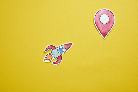 top view of paper rocket and location sign isolated on yellow 写真素材