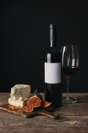 close-up view of bottle and glass of red wine, delicious cheese and figs on wooden board