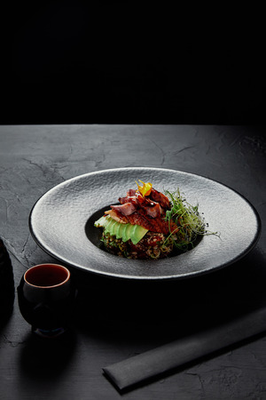 delicious Japanese Ceviche with seafood, avocado and herbs on black plate Stock Photo