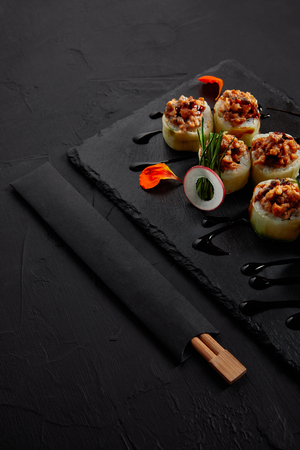 close-up view of delicious sushi roll with creamy eel and kimchi mayonnaise on slate board and chopsticks Фото со стока