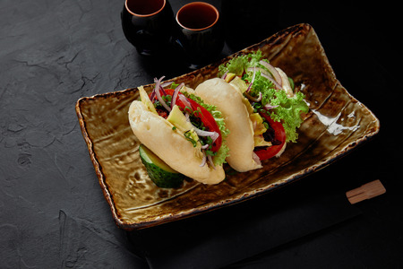 high angle view of delicious fresh buns with vegetables on plate