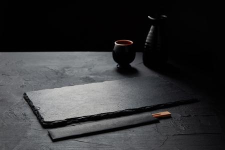 空の黒いスレートボード、箸、ジャグ、マグカップ 写真素材
