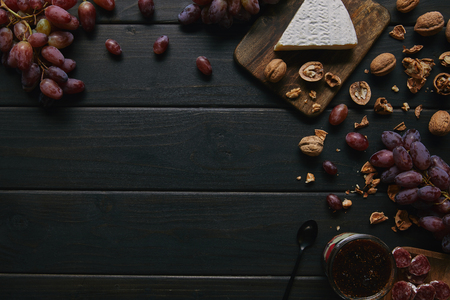 top view of fresh ripe grapes, walnuts, sliced salami, jam and delicious cheese on wooden background 스톡 콘텐츠
