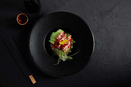 top view of delicious traditional japanese dish with seafood, avocado and herbs on black plate Stock Photo