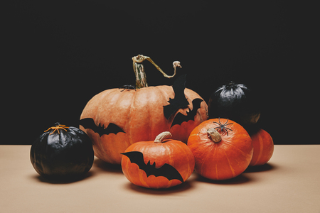 orange and black pumpkins with paper bats on table, halloween concept