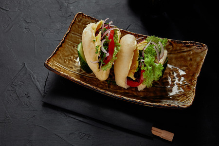 close-up view of delicious fresh buns with vegetables on plate and chopsticks