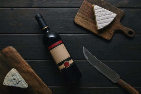 top view of wine bottle with blank label, knife and delicious cheese on wooden table Stock fotó - 108723282