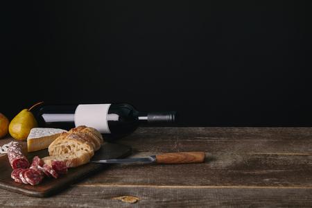 Botella de vino con etiqueta en blanco, peras, deliciosos bocadillos y cuchillo de mesa de madera Foto de archivo