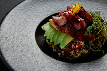 close-up view of Japanese Ceviche with seafood, avocado and herbs on black plate